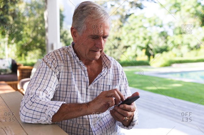 Handsome senior Caucasian man enjoying his retirement, sitting at a table in the garden in the sun text messaging with a mobile phone, self isolating during coronavirus covid19 pandemic