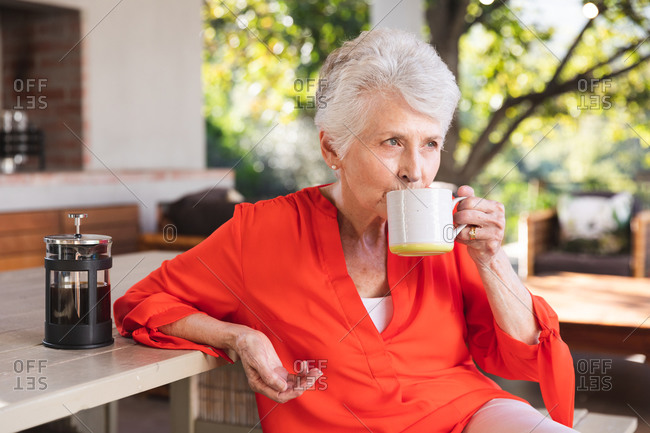 A happy retired senior Caucasian woman at home in the garden outside her house on a sunny day, sitting at a table holding a cup of coffee, looking away and smiling, self isolating during coronavirus covid19 pandemic