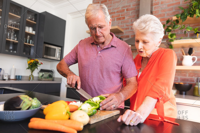 Happy retired senior Caucasian couple at home, preparing food and smiling in their kitchen, the man cutting vegetables, the woman watching and talking to him, at home together isolating during coronavirus covid19 pandemic