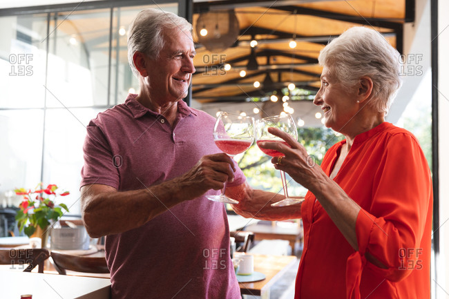 Happy retired senior Caucasian couple at home in their kitchen, standing and making a toast with glasses of wine and both smiling, at home together isolating during coronavirus covid19 pandemic