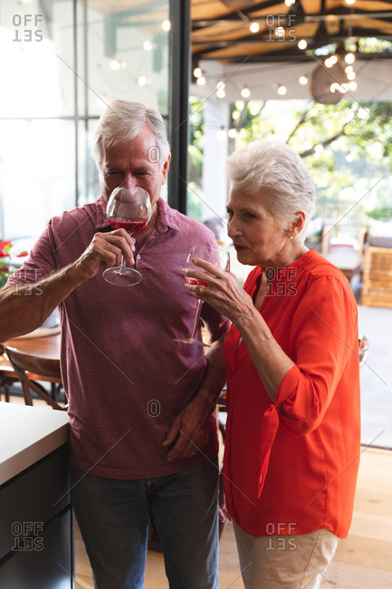 Happy retired senior Caucasian couple at home in their kitchen, standing and drinking glasses of wine and both smiling, at home together isolating during coronavirus covid19 pandemic