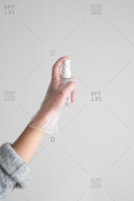 Hands spraying disinfectant spray into the air