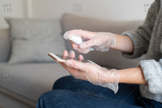Woman cleaning her cell phone with disinfectant
