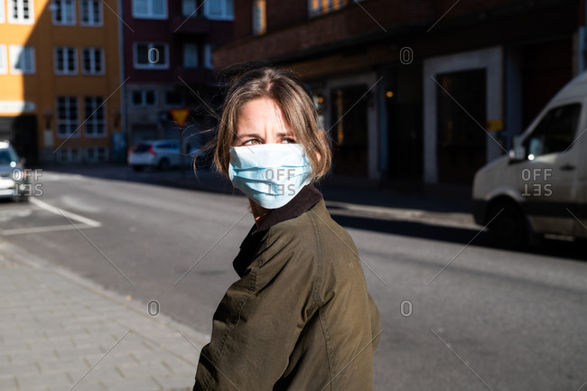 Woman on street wearing a face mask and looking over her shoulder