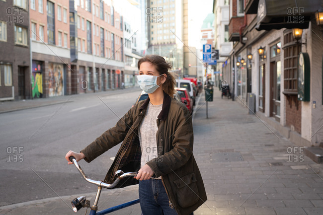 Woman on city street wearing a face mask while walking her bike