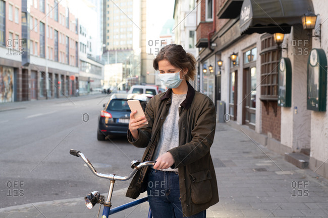 Woman on city street wearing a face mask while checking her phone outdoors