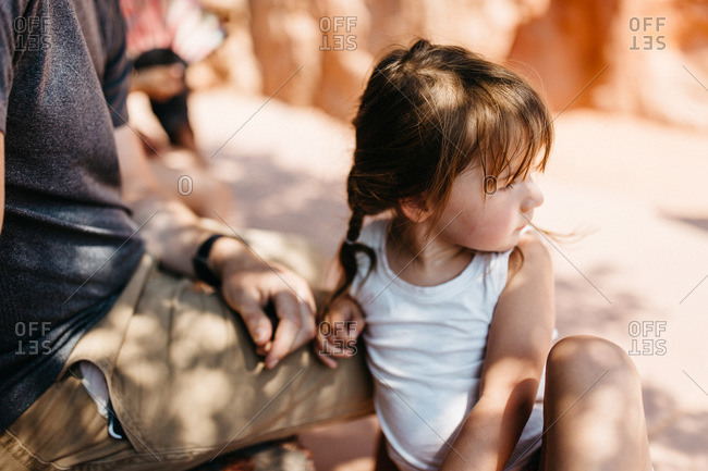 Little girl sitting by her father in the shade