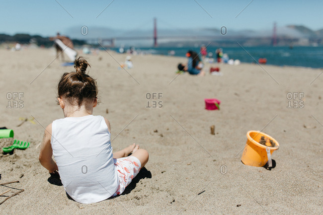 Little girl sitting in the sand playing on beach by the Golden Gate Bridge