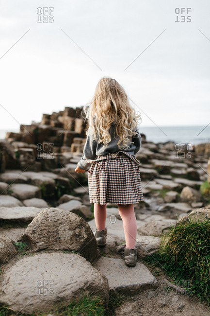 Rear view of little girl walking on stones at Giant's Causeway in Ireland