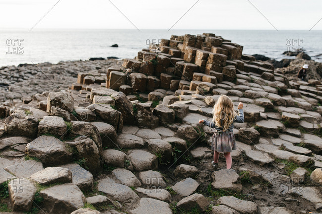 Rear view of blonde little girl walking on stones at Giant's Causeway in Ireland