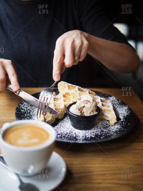 Unrecognizable person using form and knife to cut sweet waffles near bowl of ice cream and cup of coffee on table in cafe