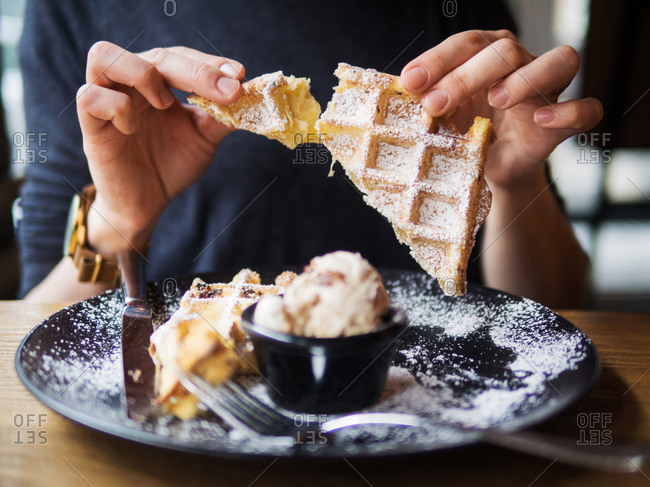 Anonymous person breaking off piece of soft waffle over plate with tasty ice cream while sitting at table in restaurant