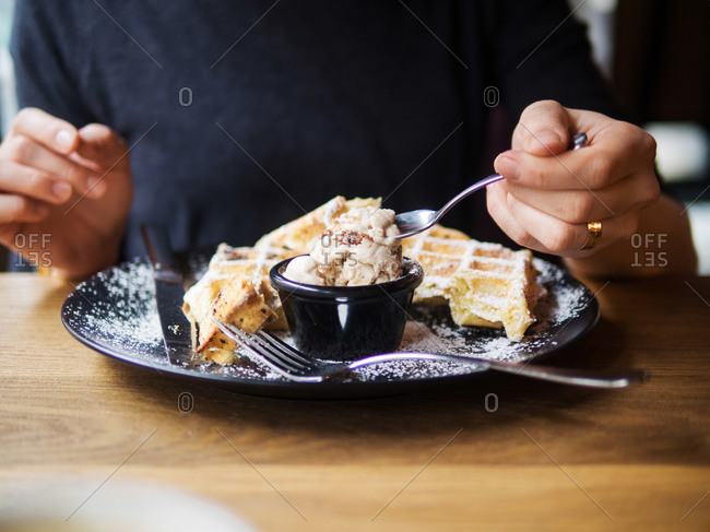 Unrecognizable person enjoying cold sweet ice cream and fresh waffles during lunch in cafe