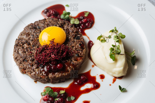 From above of delicious roasted beef steak garnished with herbs and egg yolk served with mashed potatoes on white plate