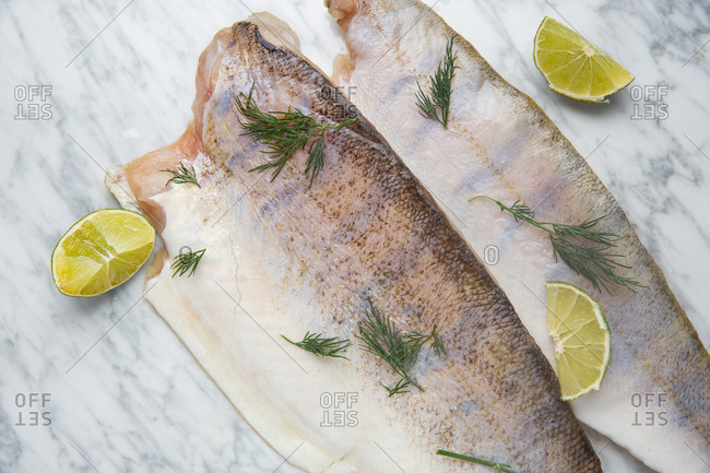 Top view of headless fish with fresh dill and pieces of fresh lime placed on marble table