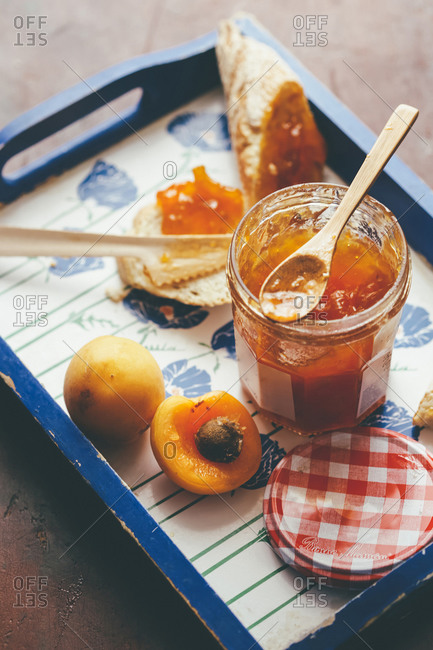 From above of delicious sweet apricot jam in glass pot served on tray with toast and fresh apricot