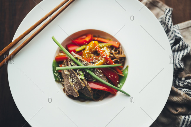 Top view of appetizing spicy Asian fried noodles with meat and colorful vegetables served in white plate with bamboo chopsticks on wooden table