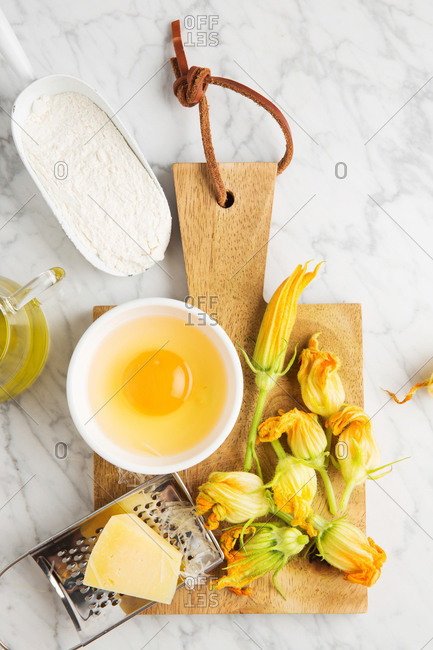 From above grater with cheese and bowl with raw egg placed on cutting board near fresh zucchini flowers and flour on marble table in kitchen