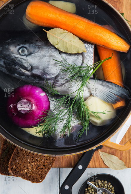 Top view of raw fish and onion placed in water inside saucepan with carrots and potatoes supplemented with dill and bay leaf during soup preparation