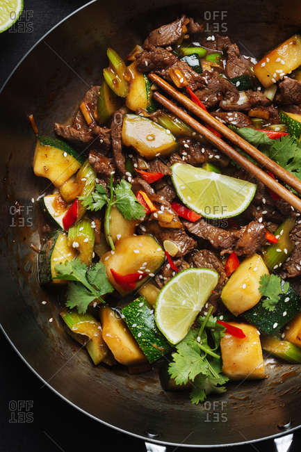 From above of Asian spicy wok stir fried dish with meat and zucchini garnished with fresh lime and cilantro