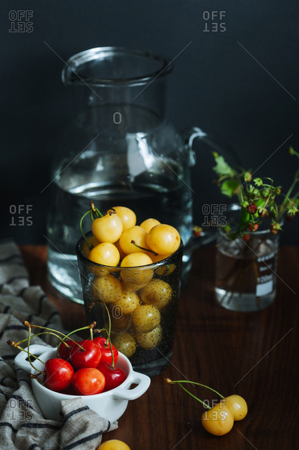 Fresh red and yellow cherry fruits in glass pots placed on wooden table near glass vase with water on black background