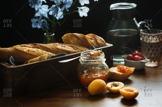Glass pot with homemade apricot jam placed near tray with fresh baguette on wooden table with fresh berries and flowers