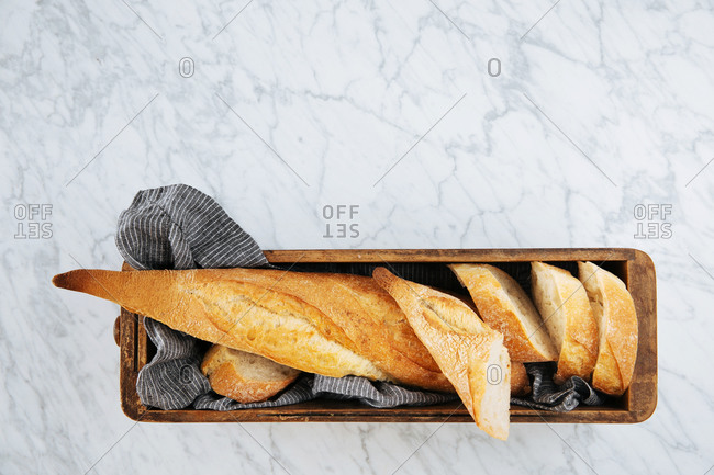 Top view of delicious fresh sliced baguette served on wooden tray placed on marble table