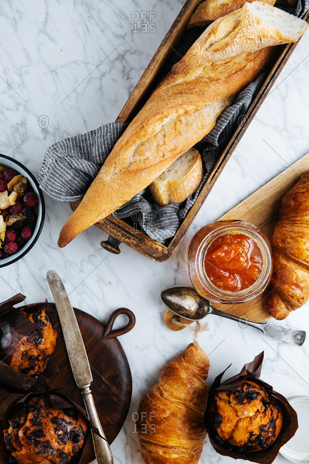 Top view composition of fresh baguette and croissants served with aromatic sweet apricot jam on marble table