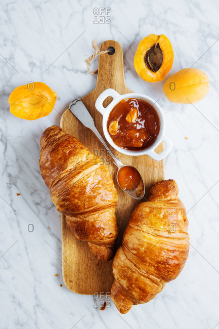 Top view of appetizing fresh croissant served with pot of homemade apricot jam on wooden cutting board placed near fresh fruits on marble background