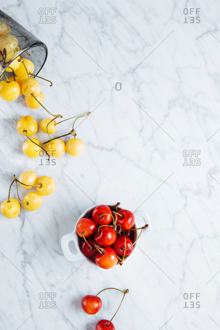 Top view of pot with fresh ripe red yellow cherries placed near fallen glass with yellow cherries on marble table
