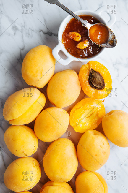 Top view of white plate with fresh yellow ripe apricots placed on white marble table with cut in half apricot and it's jam in a jar