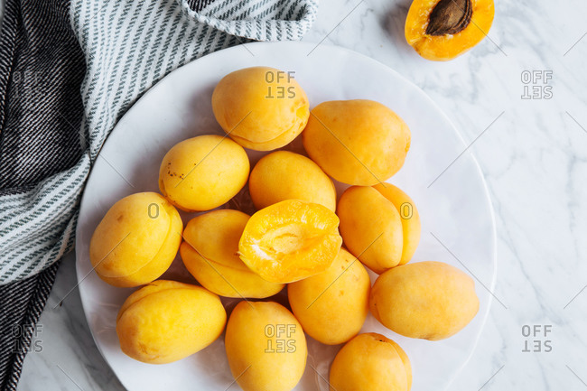 Top view of white plate with fresh yellow ripe apricots placed on plate near table cloth on white marble table with cut in half apricot