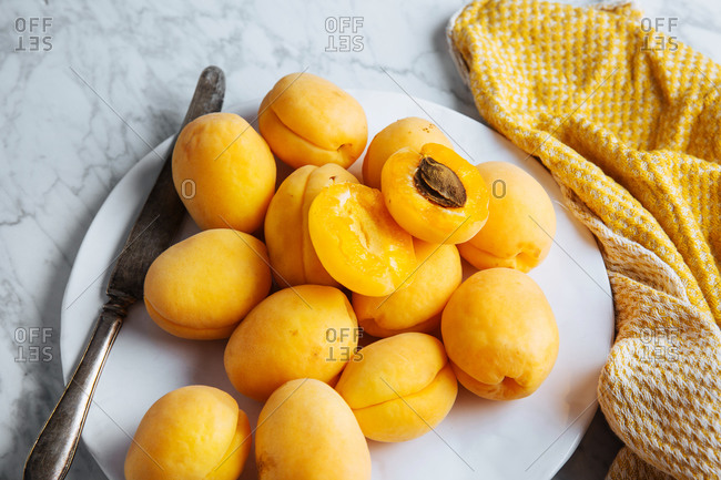 Top view of white plate with fresh yellow ripe apricots placed on yellow cloth on white marble table with cut in half apricot