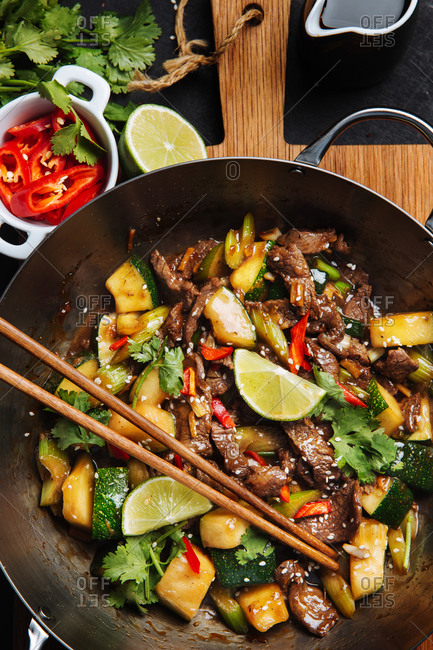 Top view of appetizing oriental spicy stir fry meat with zucchini and red pepper garnished with fresh lime and cilantro