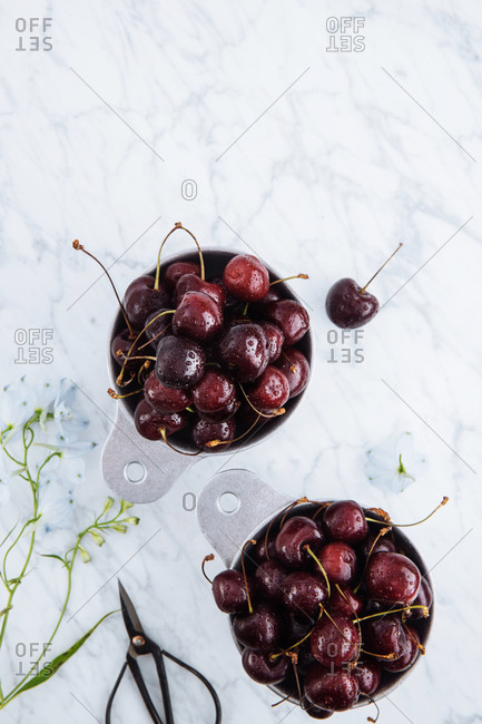 Top view of pots with ripe sweet red cherries on withe marble table with green branch