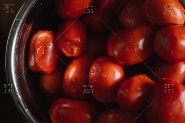 From above of fresh ripe red grape tomatoes with water drops in metal bowl placed on wooden table in kitchen