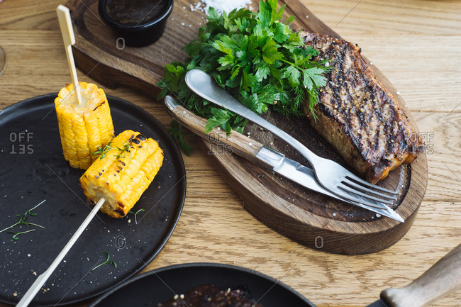 From above of delicious grilled steak served with fresh green herbs and grilled corn on sticks on wooden table