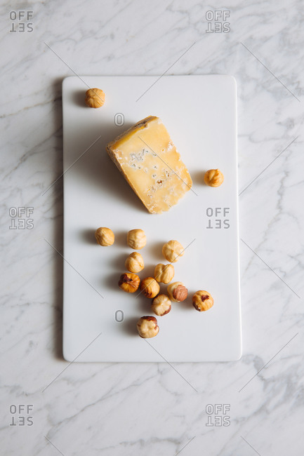 Top view of delicious gourmet blue cheese and hazelnuts served on white board on marble table