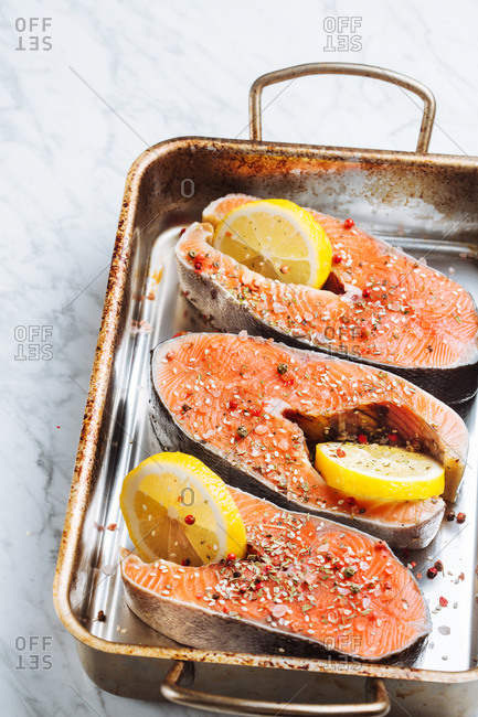Top view of fresh salmon steaks with aromatic seasoning and lemon slices placed on metal baking sheet