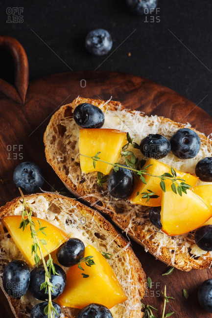 Top view of appetizing healthy sandwiches made with homemade bread and fresh apricot and blueberries garnished with thyme on wooden board on dark marble table