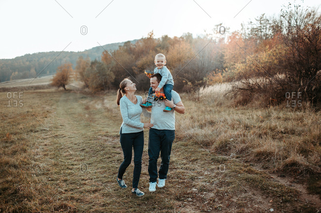 Family walking with son in field. Parents with young boy on father's shoulders walking in the countryside and smiling.