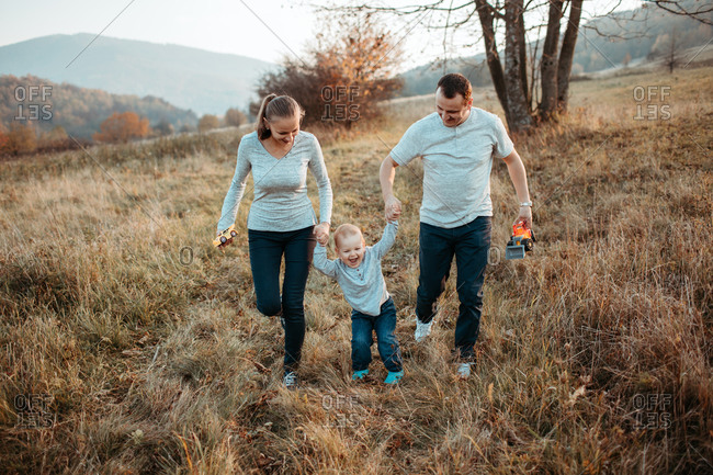 Parents holding hands with son on walk. Mother and father walking with young boy in fields and smiling.