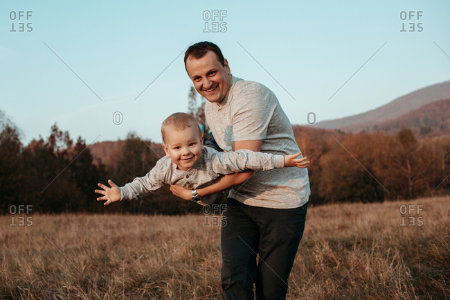 Father playing with son in field. Man smiling and holding young boy mid air with arms outstretched.
