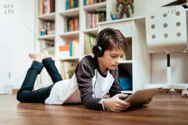 Young student wearing headphones lying on the floor studying at home working with digital tablet. Boy relaxing and online learning on digital tablet.