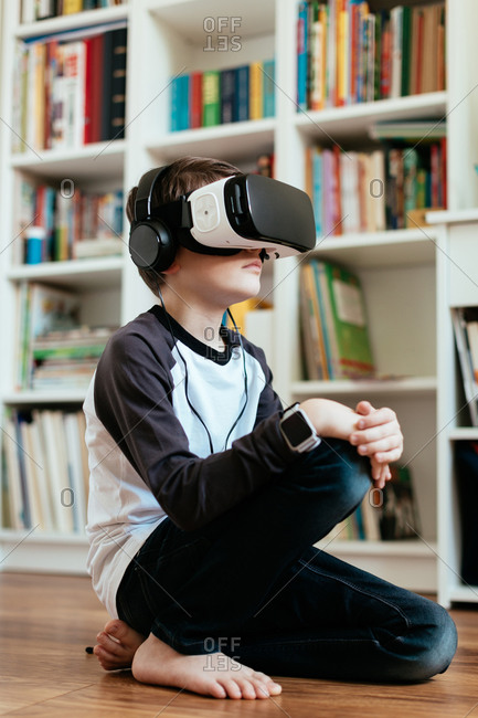 Boy sitting on the floor wearing VR glasses. Teenage boy with virtual reality headset and headphones.