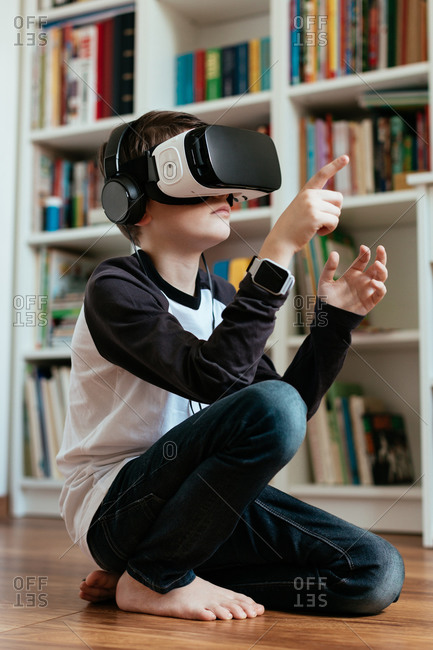Teenage boy sitting on the floor wearing VR headset. Boy wearing VR glasses with headphones and interacting.