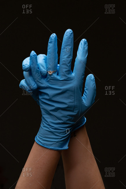 A womans hands wearing blue surgical latex gloves wearing rings on her fingers against black studio background.