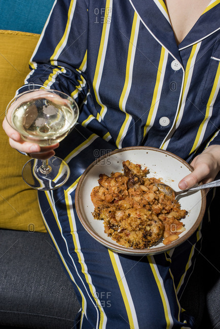 Woman in pajamas holding plate of Cassoulet and champagne