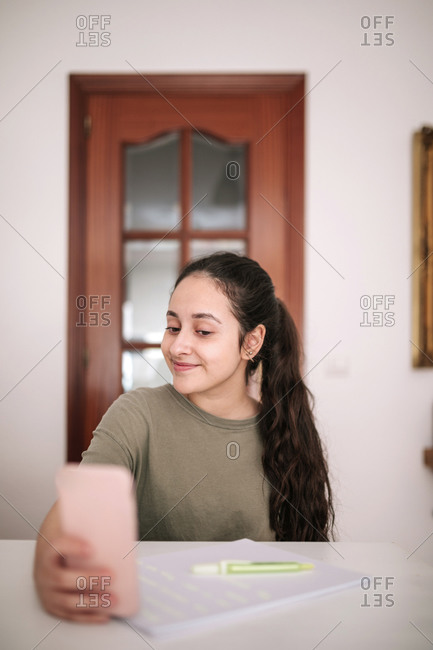 Caucasian teenage girl taking a selfie with her mobile phone at home