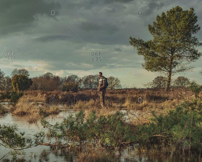Man walking in marsh under dark cloudy skies